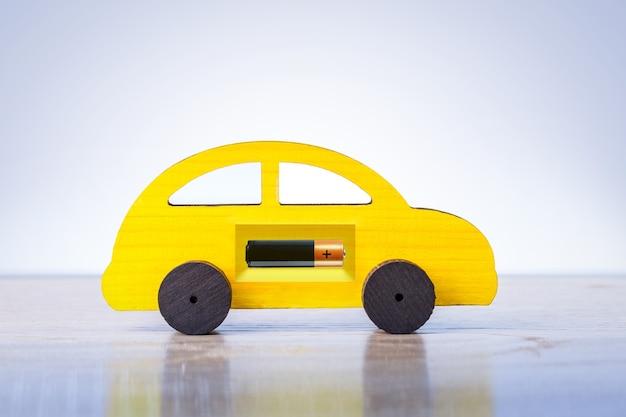 Carro yellowtoy com bateria elétrica como um símbolo de carro elétrico. eco style auto. economize energia, conceito de combustível.