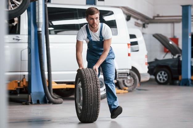Carros brancos e pretos atrás. funcionário com uniforme azul trabalha no salão automóvel