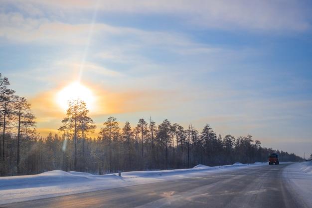 Carros circulam em uma estrada de inverno em um dia ensolarado