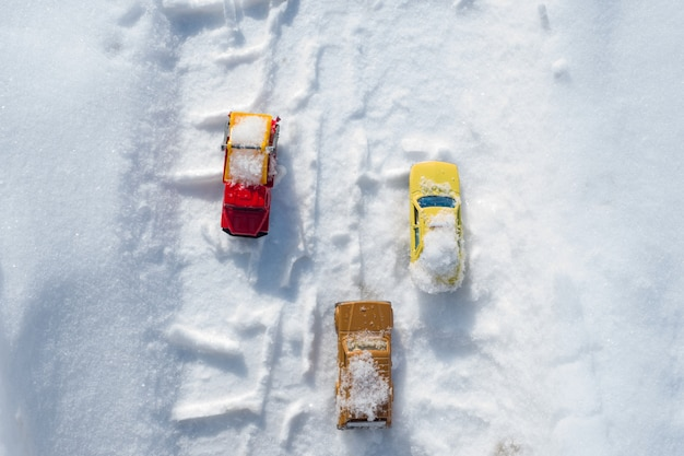 Carros cobertos de neve dirigindo pela estrada coberta de neve