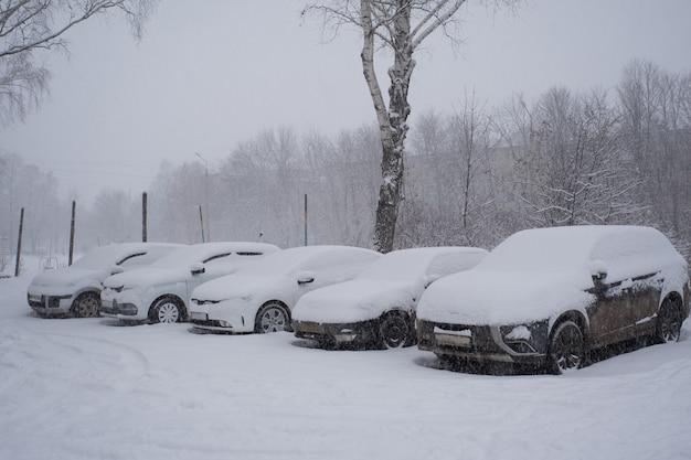 Carros cobertos de neve em um estacionamento.