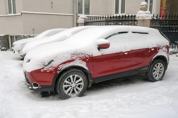 Carros cobertos de neve estacionados na rua