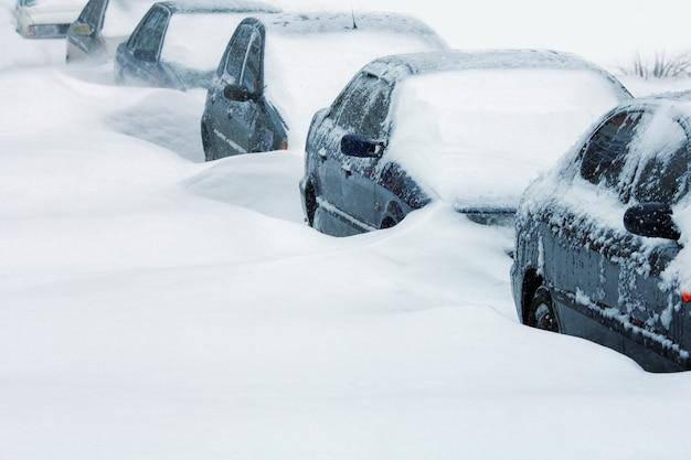 Carros cobertos de neve na estrada após uma forte nevasca