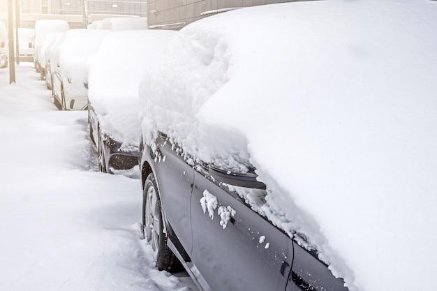 Carros cobertos de neve no estacionamento