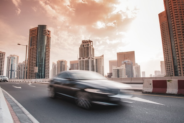 Carros com edifícios altos no fundo do sol