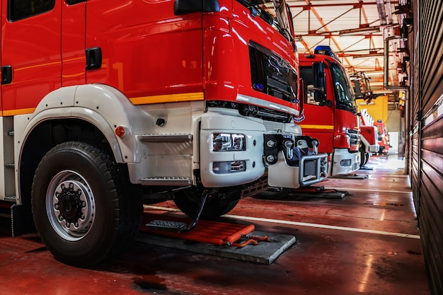 Carros de bombeiros estacionados na brigada de incêndio preparados para a ação.
