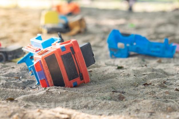Carros de brinquedo e brinquedos de plástico em uma caixa de areia com luz solar com efeito de reflexo no playground