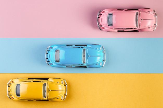 Carros de brinquedo retrô vintage pequeno em um fundo rosa, amarelo e azul