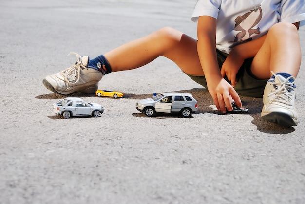Carros de brinquedos na frente de pernas de crianças