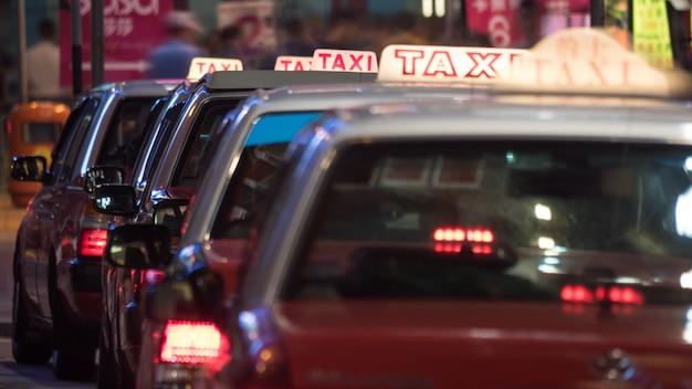 Carros de táxi estacionados em fila à noite
