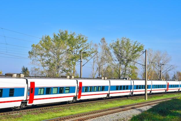 Carros de trem expresso viajando de trilho entre árvores