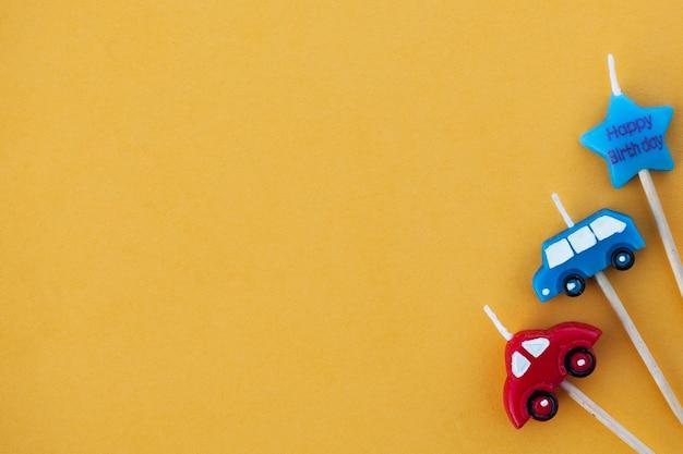 Carros de velas multicoloridos em uma superfície amarela com espaço para texto