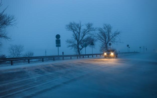 Carros dirigem na rodovia durante uma tempestade de neve à noite.