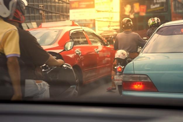 Carros e motos esperam no engarrafamento de manhã no conceito de poluição