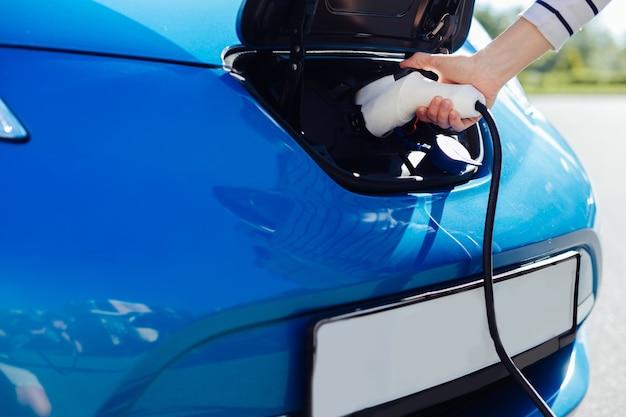 Carros ecológicos. close-up de um carregador de carro elétrico sendo usado para carregar um carro elétrico moderno