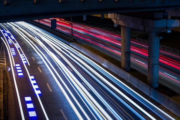 Carros em movimento rápido, iluminação, velocidade do obturador longa com um tripé