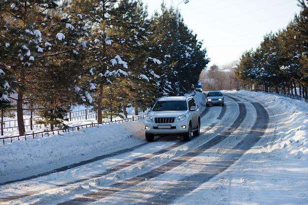 Carros em uma estrada de inverno de cidade de gelo com árvores ao redor