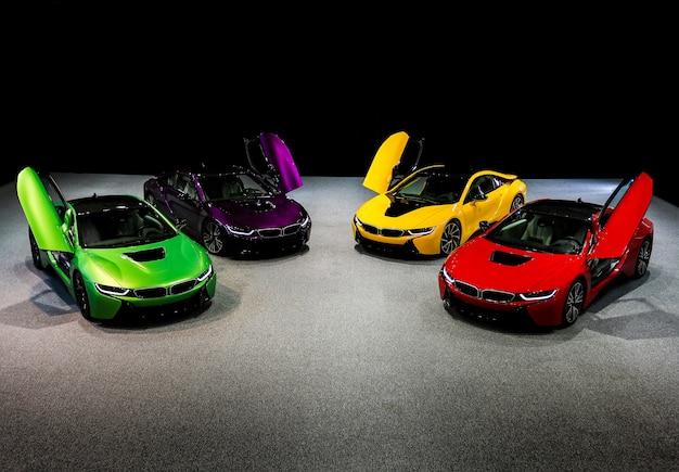 Carros esporte sedan verde, amarelo, vermelho, roxo e violeta em pé no espaço escuro
