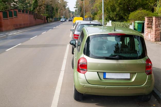 Carros estacionados ao lado de uma rua em área residencial