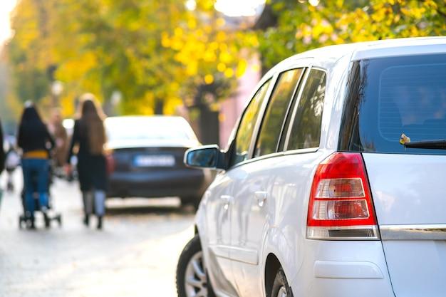 Carros estacionados em uma fileira do lado de uma rua da cidade em um dia brilhante de outono com pessoas turva, andando na zona de pedestres.
