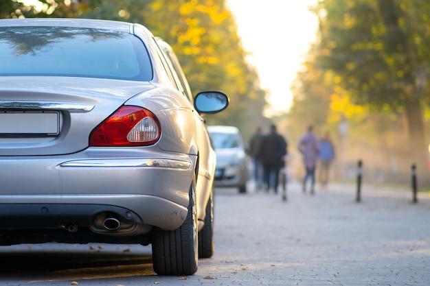 Carros estacionados em uma fileira em um lado de rua da cidade em um dia brilhante de outono com pessoas turva, andando na zona de pedestres.