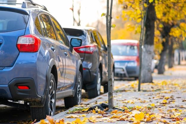 Carros estacionados em uma fileira em uma rua da cidade em um dia brilhante de outono.