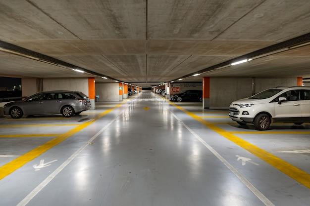 Carros modernos estacionados dentro de um estacionamento subterrâneo fechado.