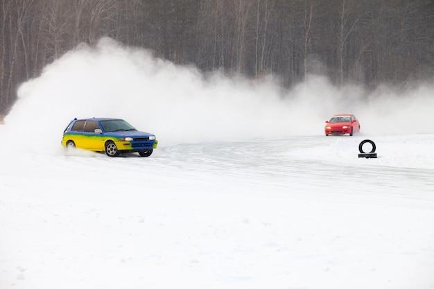 Carros movendo-se no gelo, fazendo muitos respingos de gelo durante a queda de neve