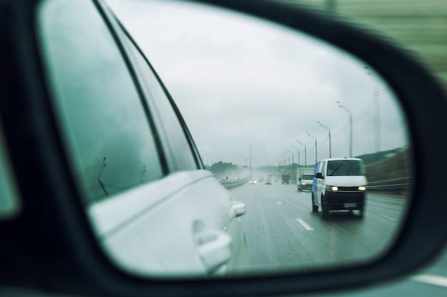 Carros na estrada na chuva no espelho lateral. fechar-se.