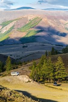 Carros off-road com turistas na estepe kurai. outono nas montanhas altai. rússia