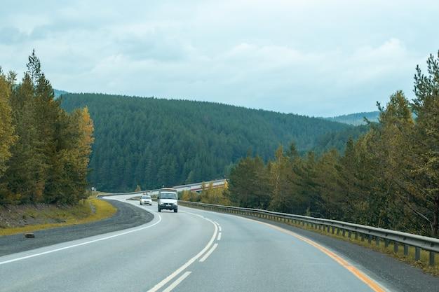 Carros passam pela estrada sinuosa da montanha da floresta no outono