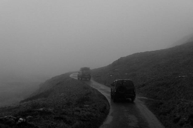 Carros passando por um terreno acidentado com fundo escuro