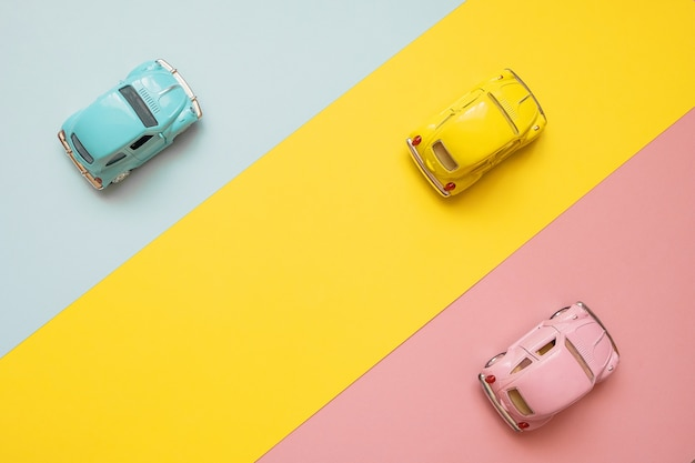 Carros pequenos do brinquedo da cor em um amarelo, em um rosa e em um azul. correndo para a linha de chegada