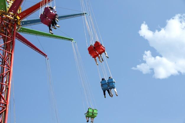 Carrossel colorido em um parque de diversões contra o céu azul