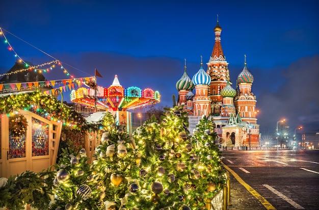 Carrossel de ano novo e árvores de natal perto da catedral de são basílio, na praça vermelha de moscou, em uma noite de inverno