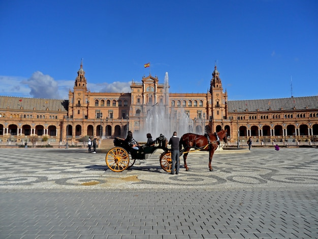 Carruagem puxada a cavalo na frente da fonte de vicente traver na plaza de espana, em sevilha, espanha