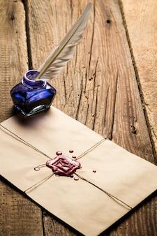 Carta antiga com pena e tinteiro na superfície de madeira