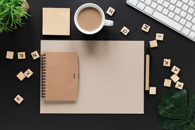 Carta blocos de madeira; xícara de chá; notas adesivas; diário; papel de cartão e teclado na mesa preta