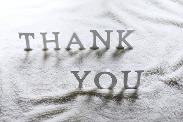 Carta branca de madeira obrigado no tapete amassado no chão