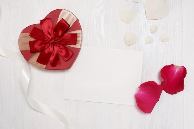Carta com um presente sob a forma de um coração e rosas