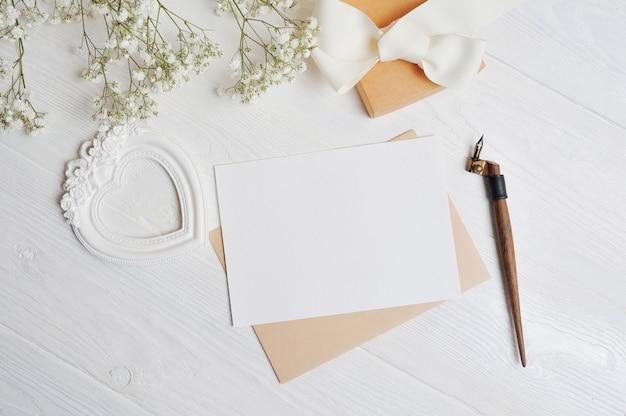Carta com uma caixa de amor em forma de um coração encontra-se em uma mesa de madeira branca com flores gypsophila