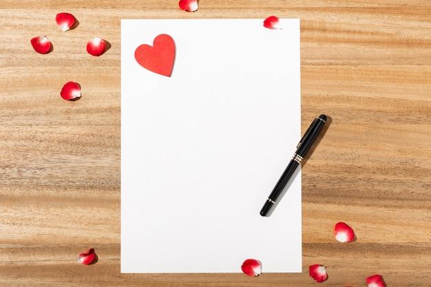 Carta de amor. cartão branco, forma de coração vermelho e caneta na mesa de madeira. postura plana. vista do topo.