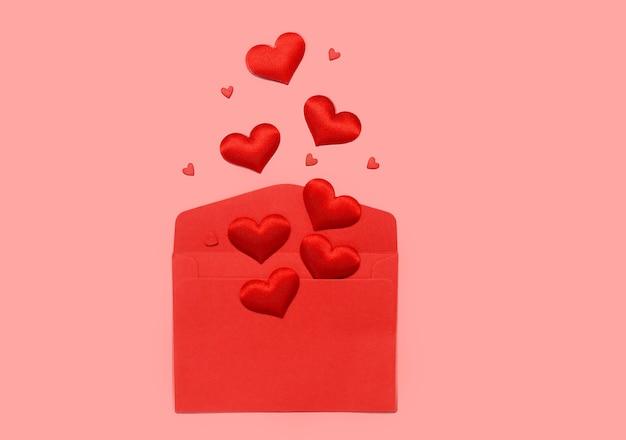 Carta de amor de dia dos namorados. envelope vermelho em branco e corações em um fundo rosa.