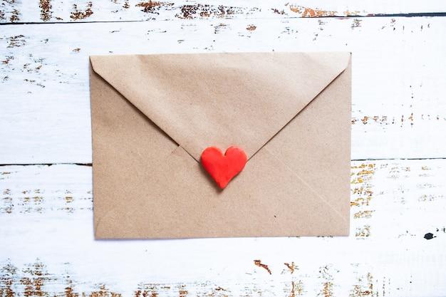 Carta de amor em um envelope artesanal com coração de argila vermelha em fundo branco de madeira.