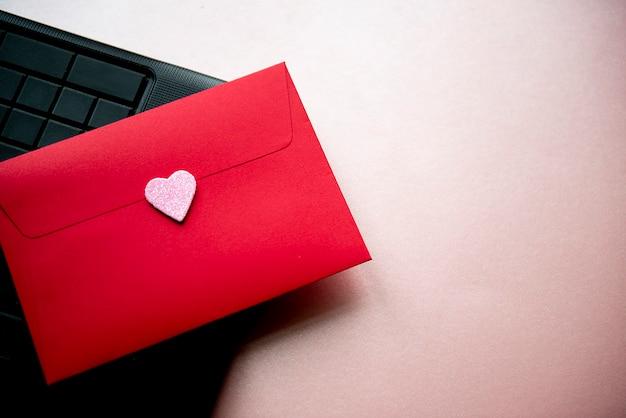 Carta de amor em um envelope vermelho com um coração rosa em um teclado preto de laptop, vista superior