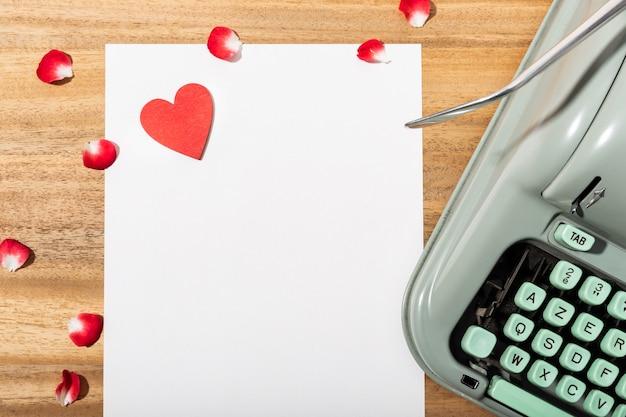 Carta de amor. mesa com papel em branco, máquina de escrever retrô e coração vermelho