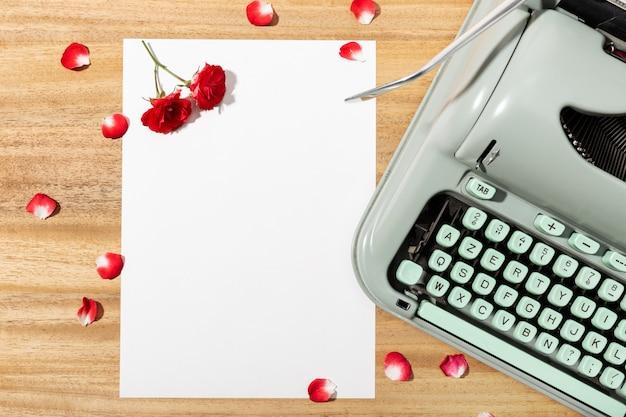 Carta de amor. mesa com papel em branco, máquina de escrever retrô e rosas vermelhas e pétalas