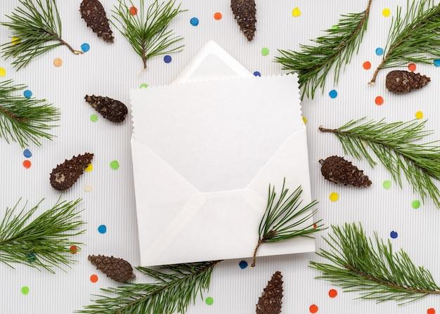 Carta de cartão de natal. folha de papel branco com espaço de cópia para o texto. decoração de ramos de pinheiro e confetes festivos