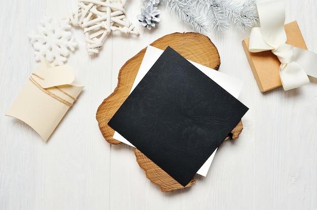 Carta de cartão preto de natal de maquete em envelope e presente com árvore branca