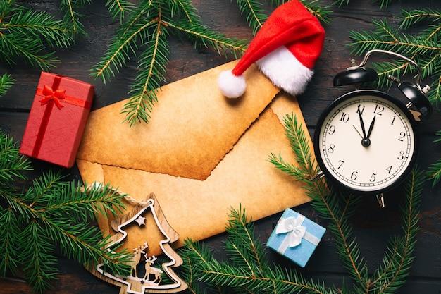 Carta de envelope antigo em branco com galhos de árvore de abeto de natal com despertador vintage, caixas de presente, veados e chapéu de papai noel.